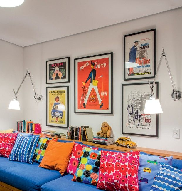 Quarto de brincar. O enorme sofá com gavetões guarda os brinquedos. Sobre eles, almofadas com tecidos Marimekko executadas pela Trama Casa. Na parede, pôsteres adquiridos em antiquários. Para ler, luminárias Tolomeo, da La Lampe.