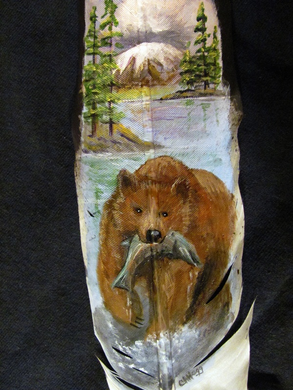 A close up of one of Cindy's meticulous paintings on an imitation Eagle feather. Bear in mountain stream with fish. http://greaseandgrace.com/