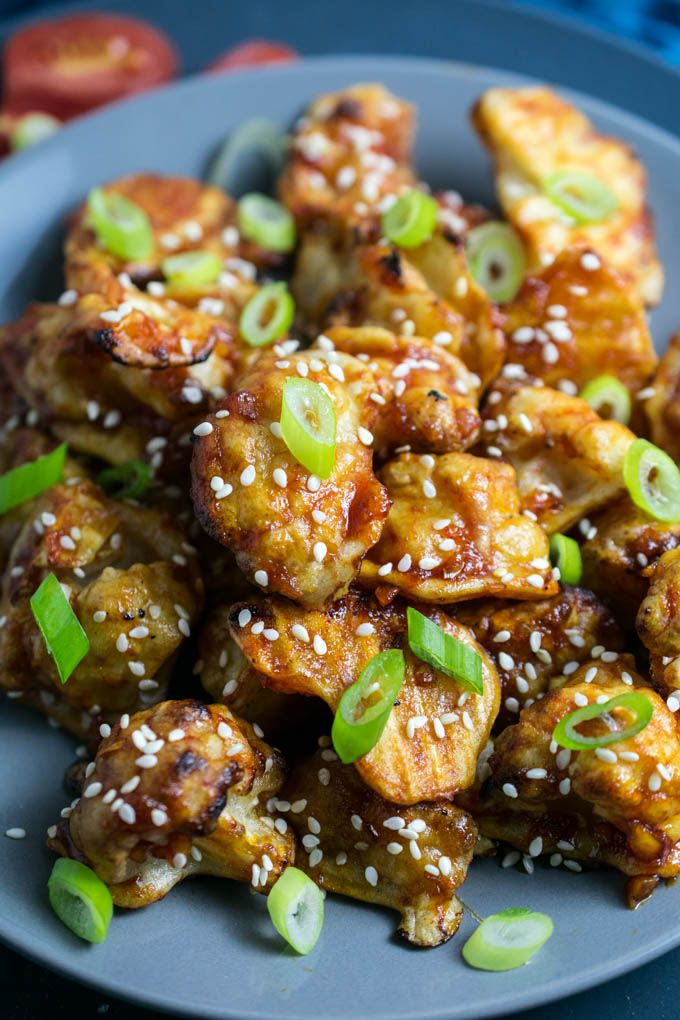 Sticky Sesame Cauliflower   Yup, it's Vegan. Baked battered cauliflower smothered in a sweet and spicy sauce.