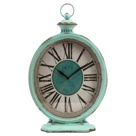 "Add a vintaged touch to your desk or mantel with this charming distressed table clock, showcasing Roman numerals and a teal finish.  Product: Table clockConstruction Material: Metal and glassColor: Teal, white and blackFeatures: Roman numeralsAccommodates: Batteries - not includedDimensions: 18"" H x 11.25"" W x 4"" D"