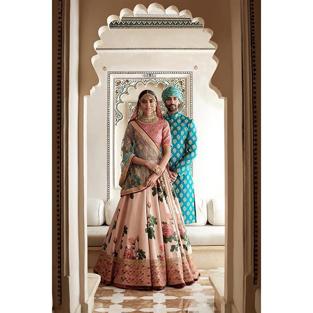 Sangeet Lehengas - Sabyasachi Pink Floral Bridal Lehenga with Gold Dull Embroidery and Blue Detailing | WedMeGood | Groom in a Bright Blue Sherwani with a Blue and Gold Safa #wedmegood #indianbride #indiangroom #indianwedding #sabyasachi #pink #lehenga #sherwani #safa #blue #coupleshot