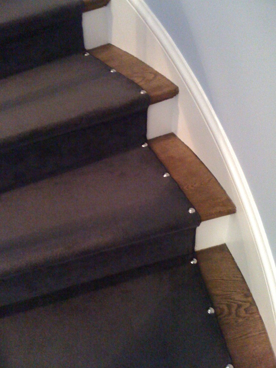 oversized upholstery nails on stair runners. nice hall detail