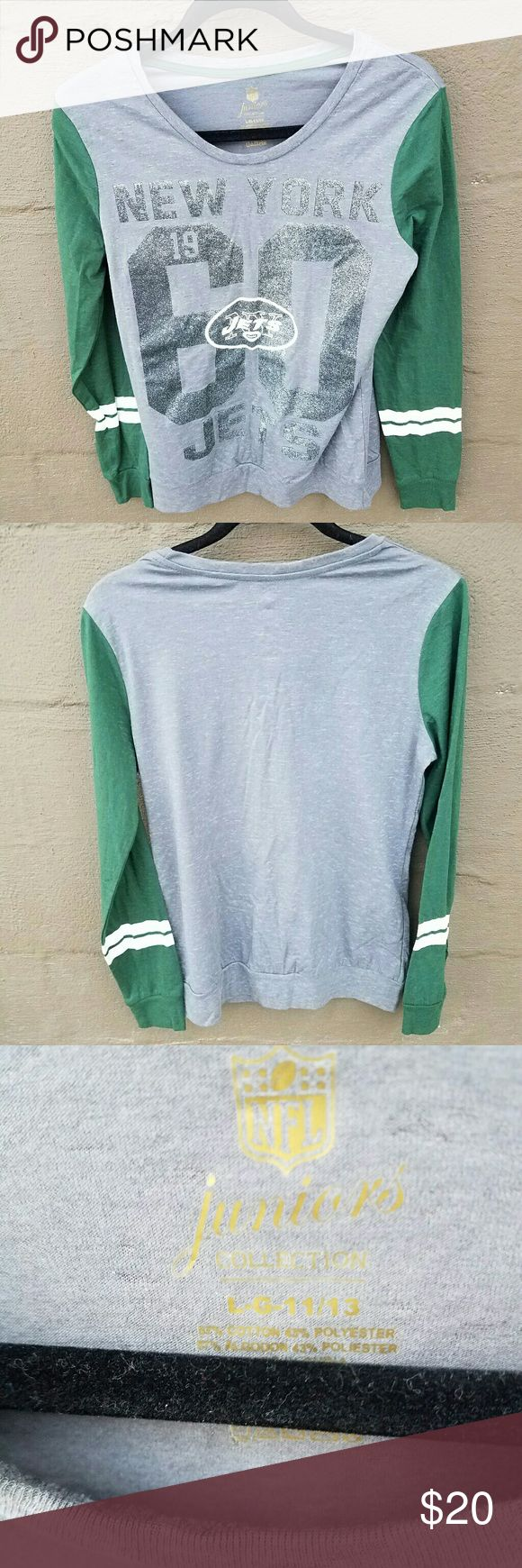 NFL Jets gray and green raglan long sleeve shirt This NFL gray and green long sleeve NWOT shirt is a size large. It has glitter lettering and by NFL Juniors Collection. It is made of 57% cotton and 43% polyester. NFL  Tops Tees - Long Sleeve