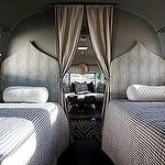 Swanky Airstream trailer made chic! bedrooms - vintage camper Moroccan silhouette twin headboards black white gingham bedding West Elm Kite Kilim Rug  Glamping! Chic, vintage camper