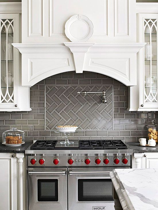 Gray porcelain subway tiles create drama against pure white cabinetry. Behind the range, a herringbone-pattern inset on the backsplash breaks up the backsplash and adds another focal point to the wall./