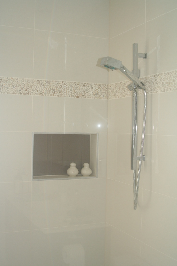 Designed by White Pebble Interiors  Petite pebbles create a feature and texture in a neutral bathroom, along with the use of a contrast tile in the recessed shelf.