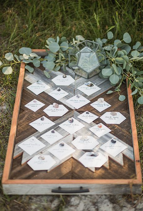Repurpose an old wooden drawer to hold geometric seating cards. Lush greenery and a shapely terrarium drive home the natural vibe.