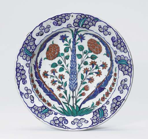 AN IZNIK POTTERY DISH OTTOMAN TURKEY, CIRCA 1580-90 With sloping rim, the white interior with a central cypress tree flanked by radiating floral sprays and enclosed with saz leaves, the rim with stylised wave and scroll motifs, the underside with alternating paired tulips and rosettes, 11¾in. (30cm.) diam.
