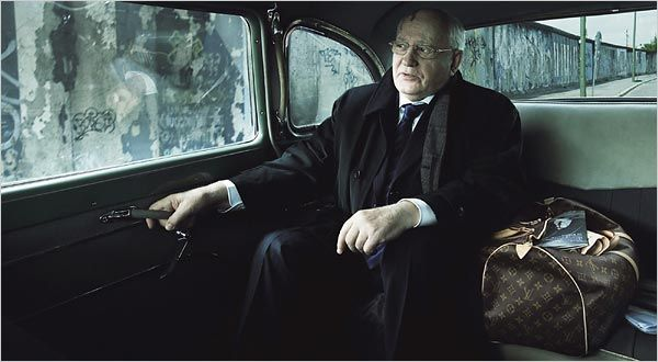 """Mikhail S. Gorbachev, the last leader of the old Soviet Union, sits in a limousine as it passes a remaining part of the Berlin Wall, poking out of the bag is a publication with the headline, """"The Murder of Litvinenko.."""""""