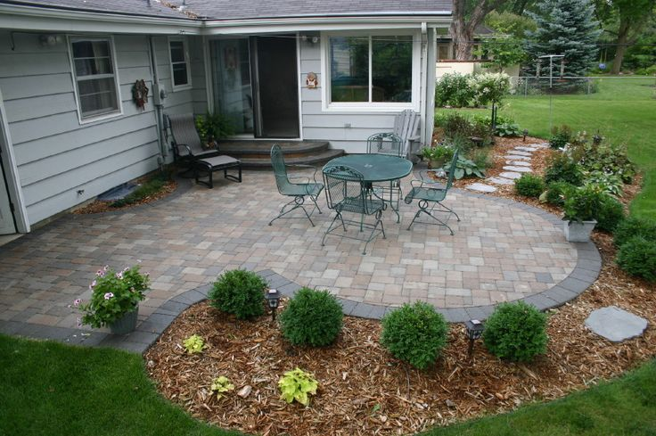 Stone Color Darker Edging Curve Of Patio With Planting In Curve