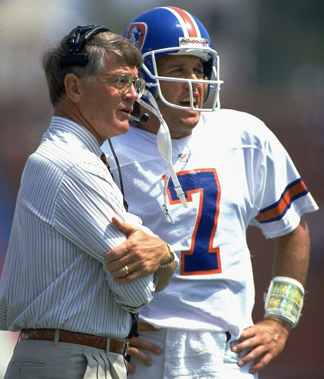 Denver Broncos Head Coach Dan Reeves on the sideline talking to his star QB John Elway , possibly the best QB to play in the NFL
