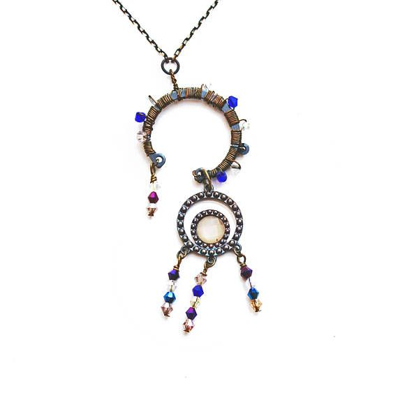 This boho beaded necklace features a circular recycled metal dial which is wire wrapped with bicone blue, citrine and clear crystal beads. A pendant with an acrylic gem and dangling bicone crystal beads dangles at an angle from the metal dial. The lovely asymmetrical pendant has