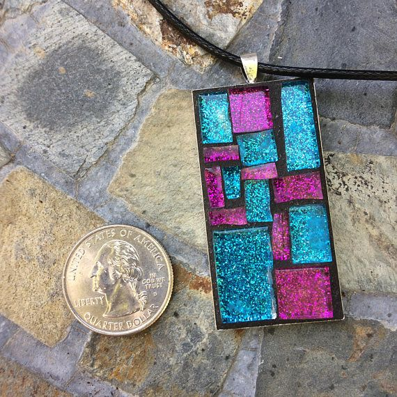 This handmade, one-of-a-kind mosaic necklace pendant features hand-cut violet and indigo glitter glass. Black grout was used to bring out the colors. Grout sealant was used to protect this work of art. The pendant features a rectangular silver bezel tray measuring 1 x 2 (25 x 50mm).