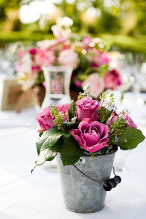 Rose centerpiece in tin pail. Love the combo of elegant and rustic.