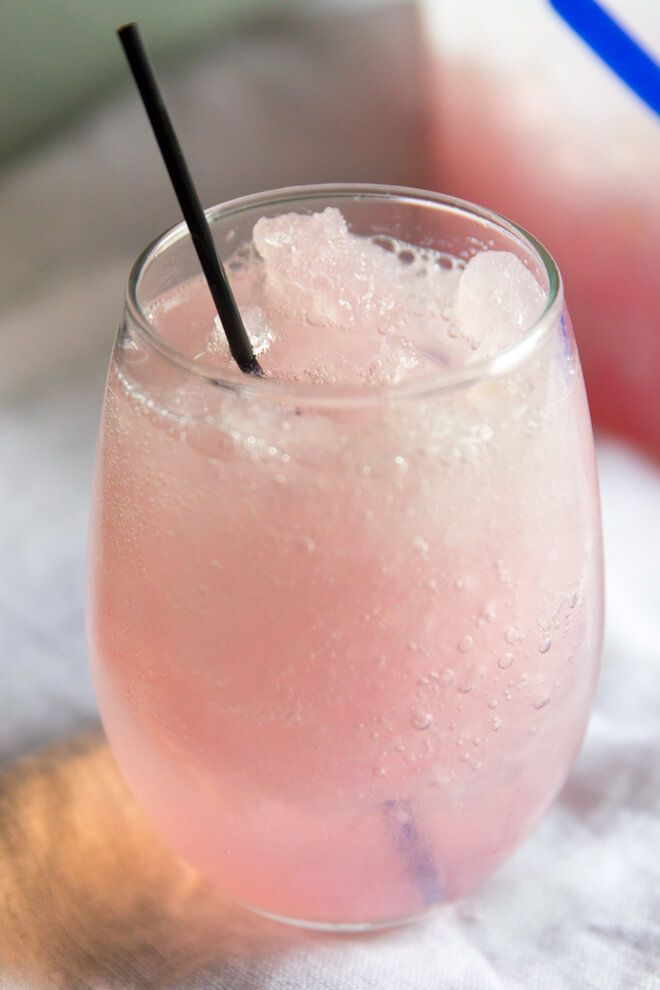 Pink lemonade vodka slush in a stemless wine glass with a small cocktail straw. The slush has bubbles in it, and is light pink in color. In the background on the right is a ice-cream tub with the pink lemonade vodka slush. It is pictured on an off-white linen background.