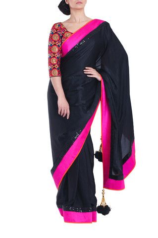 VIKRAM PHADNIS Bold, satin georgette saree in jet black with stunning pink/orange raw silk borders. Features black sequin work throughout. Contrasting semi-stitched, raw silk blouse with 3/4 length sleeves included.  Blouse is fully embroidered in multi-coloured resham thread work with antique gold sequins. #Saree #Sareeblouse #Bollywoodfashion #Designer