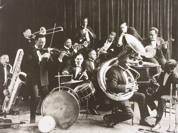 "Type of source: photograph  1920s was well known as "" Jazz Age"". Jazz was a type of music that originated in New Orleans in U.S in early 1900s. It is characterized by its improvisatory nature, rhythmic vitality and emotional expressiveness. Jazz influenced popular culture, like Jazz poetry. The status of African Americans was elevated, because at that time, many African artists appeared on the stage. Retrieved from  http://www.thecanadianencyclopedia.ca/en/article/jazz/"