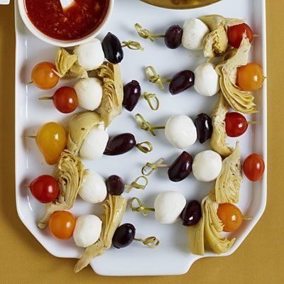 How adorable are these Mediterranean appetizer-style skewers? Simply pop tomatoes, artichokes, olives, and mozzarella on a toothpick for thos super simple party starter. Recipe here. | Health.com