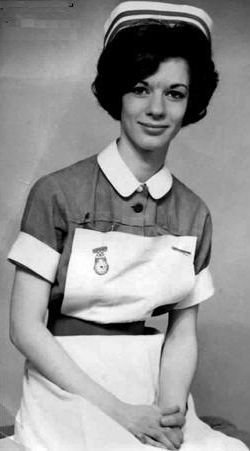 """Great Britain Staff Nurse, 1970's. In the UK, in the NHS, most all nurses wear uniforms of specific colors to help others identify her """"rank"""" within the hierarchy of nursing staff. Most all nurses, whether student or graduate nurse, wore white aprons to protect their uniforms, and a pin watch pinned to the upper right of the bib portion for use in counting pulse, respiration, or IV drip rates, instead of wristwatches."""