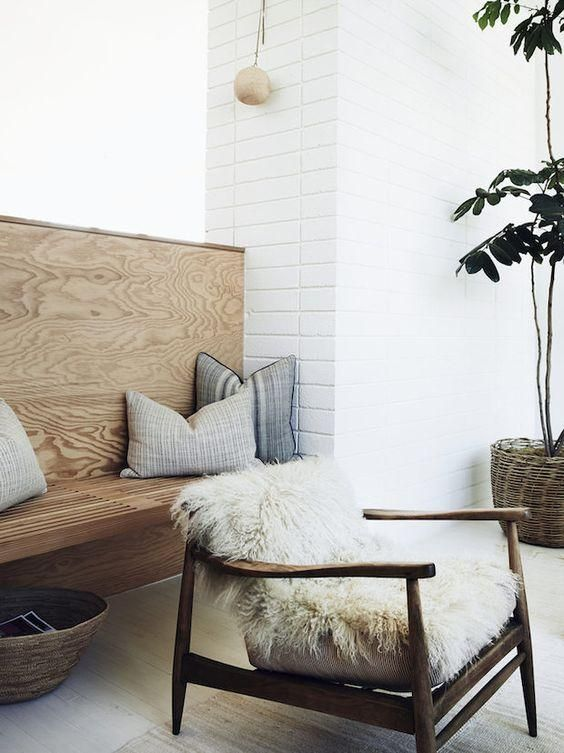 Mid-century wood arm chair draped with a white fluffy sheepskin and rustic built-in seating nook, decked out with vintage batik gray and white striped and patterned pillows, in a fabulous mid-century modern home in Los Angeles.