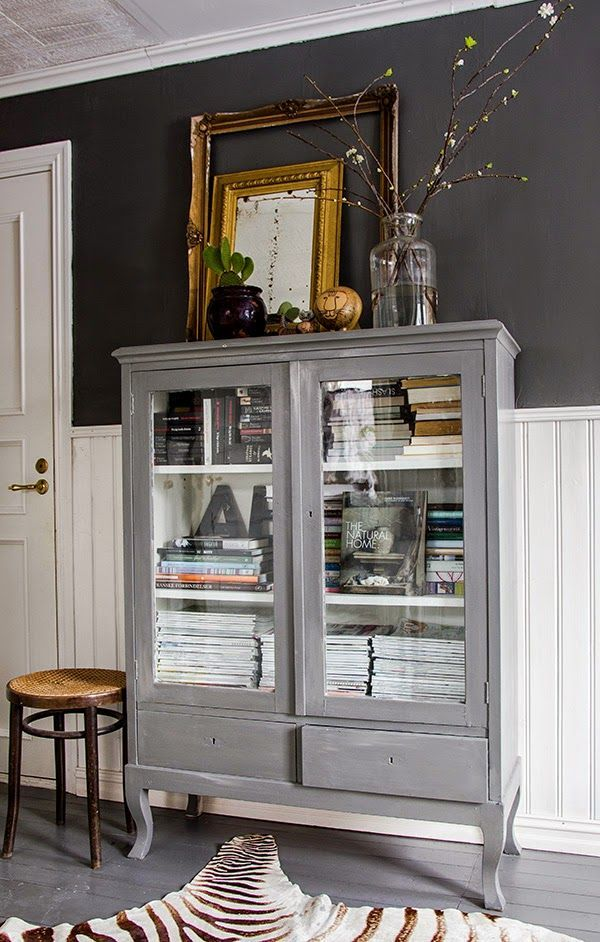 Gray wood glass front cabinet style with books, objets, antique frames, and vases. The dark gray wall color adds a nice contrast - Home Decor Details
