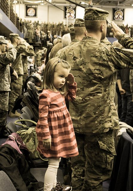 Daniella, salutes behind her father, Capt. Dan Moen of 1-89 CAV, 2nd BDE, 10th Mountain Division, during the National Anthem at his deployment ceremony on January 11, 2013, at Fort Drum, NY. Photo by Sasha Moen