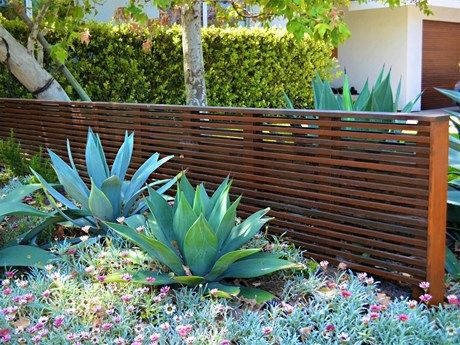 This fence is more about looks than function. Thin strips of wood running horizontally serve as a screen that separates the garage and parking area from the rest of the property. The designer then planted sculptural succulents, using the fence as a backdrop. Notice that the stain color used matches the finish on the garage door.