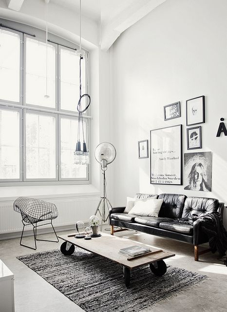 This white industrial living room is a beautiful modern space. The cushions and rug give the room warmth and cosiness.