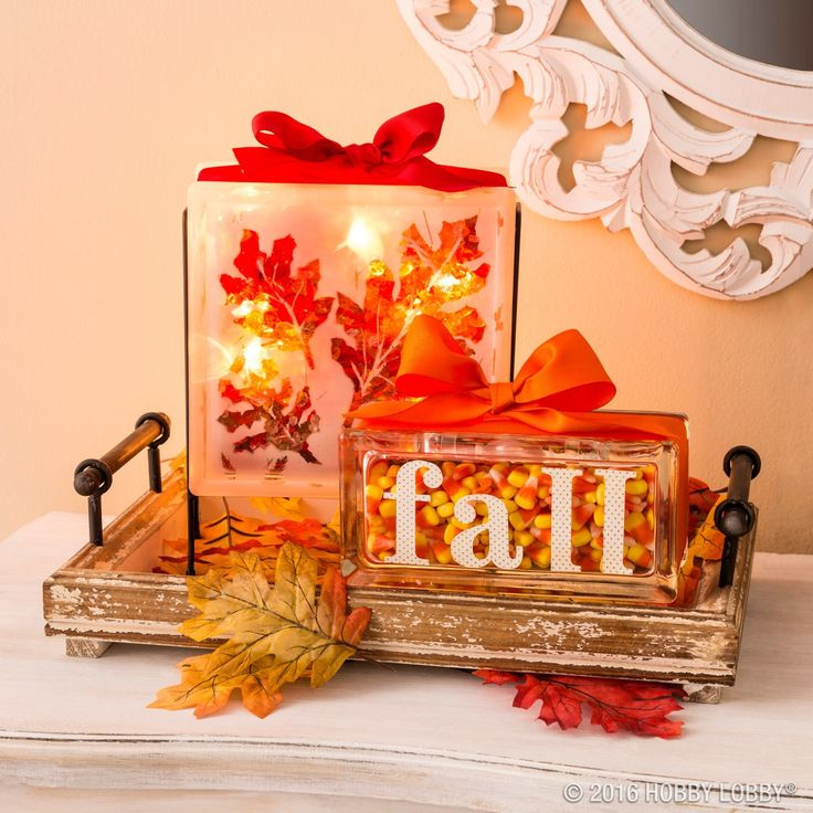 Fancify your fall foyer with glass blocks!  To create glass blocks with stenciled leaves: 1) Draw outline of autumn leaves on sticker paper, cut out leaf shapes and stick to glass block surface. 2) Spray frosted glass finish (SKU: 237826) on glass block. 3) Remove stickers to reveal leaf shape. 4) Fill block with crushed glitter glass filler (SKU: #940478) and add strand lights if desired. 5) Embellish with ribbon and a bow.