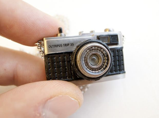 it's a tiny Olympus Trip 35 camera crafted from multiple pieces of brass, and the various components actually work!