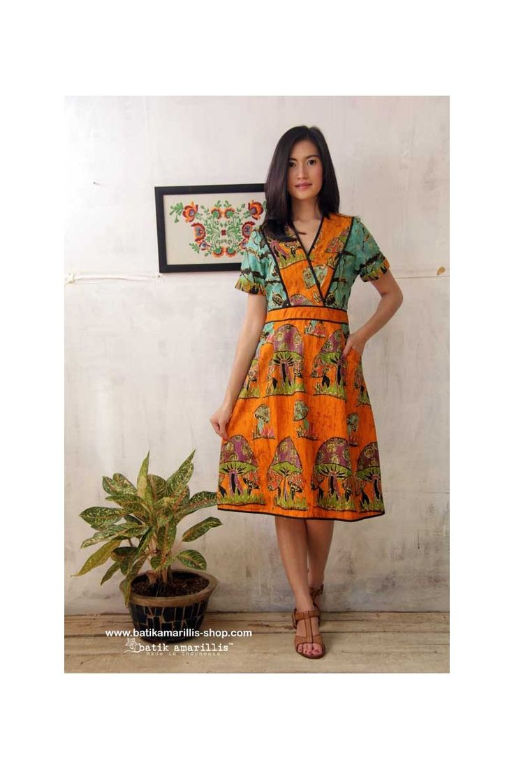 batik amarillis's primavera dress The design offers a chic take on pinafore styling with its cross-over bodice also it has a cross-over V-neck and contrast accents and zip fastening at the back of the dress.