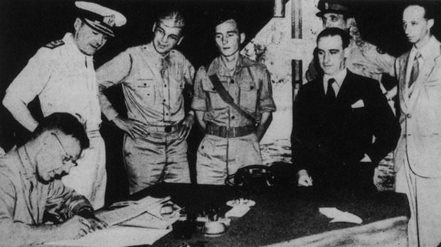 Italian General Giuseppe Castellano signing, on behalf of Italy, the Italian armistice at Cassibile, Sicily, on September 3, 1943. Looking on are Italian aide Luigi Marchesi, left, and General Walter Bedell Smith.
