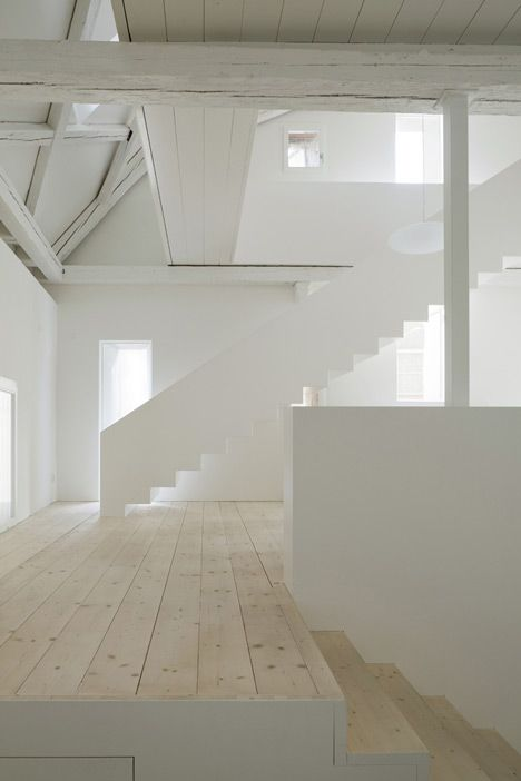 Metal framed staircase connects white-washed offices in this studio for Huesler Architekten