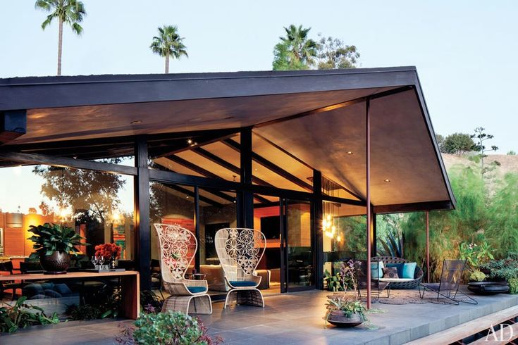 AD features John Legend's fabulous Hollywood Hills home with inviting indoor/outdoor living space with full length floor-ceiling windows with sliders provide an outdoor extension of the interior - both emphasizing organic, tactile materials and finishes. B Italia armchairs on the terrace. Don Stewart, architect.