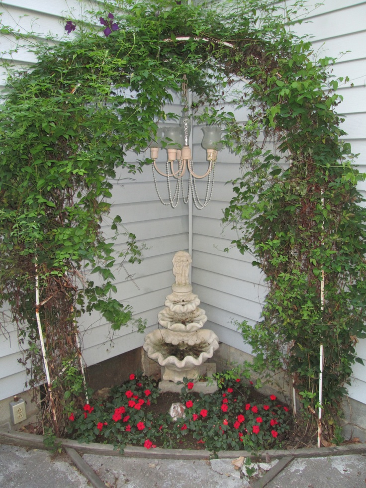 ...Stone water fountain with rusty arch of clematis and repurposed ...