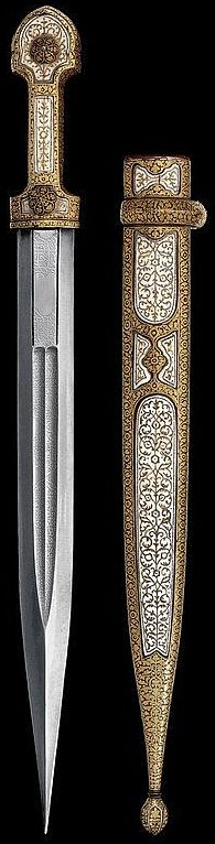Caucasian kindjal, circa 1900, double edged double groove blade with long Arabic inscriptions, a riser on the tip; iron grip, completely koftgari-decorated in gold with floral motifs, the upper part with three openings, ivory-inlaid and decorated in gold; two flower-shaped rivets. Cloth covered sheath, iron with openings inlaid with ivory-plaques, decorated en suite; grooved pine-cone shaped chape.