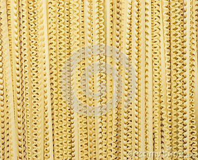 A background of curly lengths of dried yellow pasta.