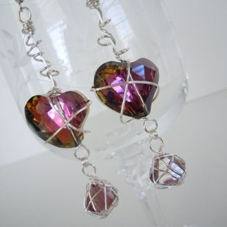 """UNIQUE """"One of a Kind"""" Gorgeous sparkly purple Crystal Heart Earrings that shine multi-coloured in the Light. The Hearts are wrapped in tarnish reistant silver plated wire and beneath are dangling pale Crystal bicones wrapped in a wire cage. Length 7cm x 2cm wide. Drop 9cm. Hand Crafted """"One of a Kind"""". VALENTINES DAY GIFT."""