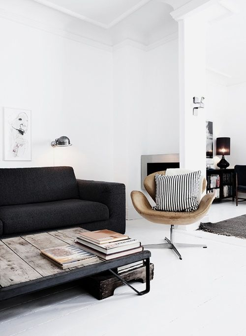 living room black sofa white walls and flooring fireplace