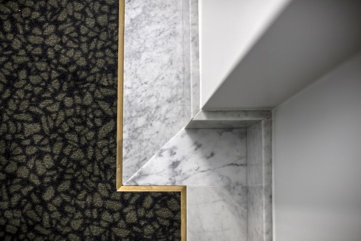 The guest rooms have brass-edged Carrara marble skirting and terrazzo-patterned custom carpeting. Photograph by Paul Bowyer.