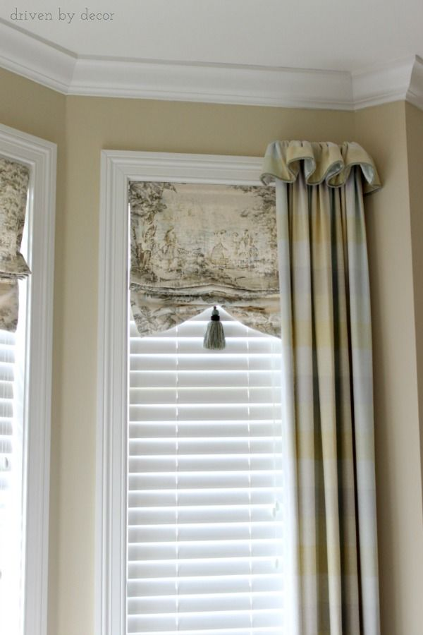 Bay window with faux shades and drapes framing ends