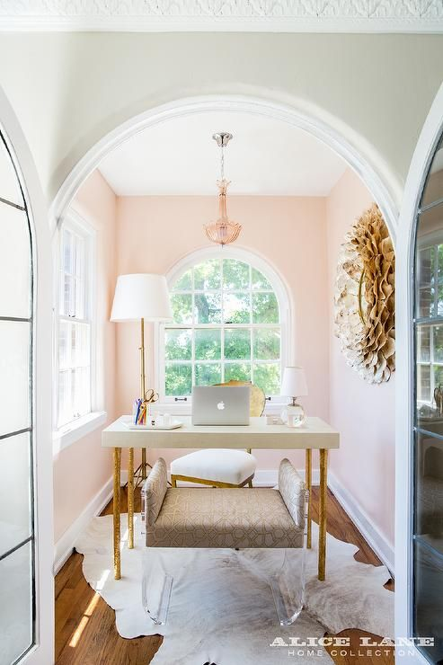 Arched French doors open to a small pink home office is clad in pink walls painted in Farrow & Ball Pink Ground framing a palladian window centered on the back wall behind a cream colored desk with gold leaf legs.