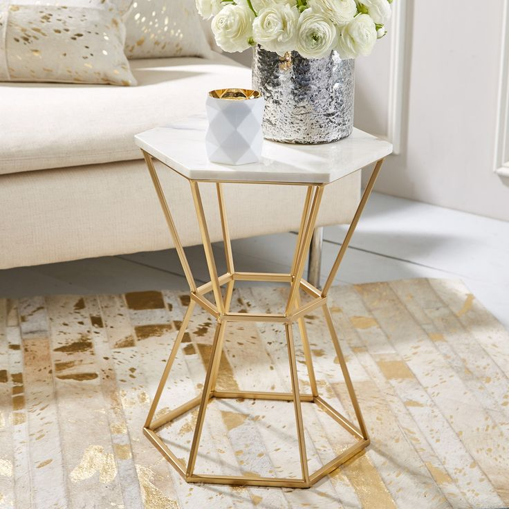 """Geometric intrigue defines the modern appeal of the Hexagonal accent table set. These sleek furnishings boast gold-finished bases, cinched in the center for a unique angled hourglass silhouette. White marble tops lend stately detail and an opulent effect. Set of 2; Marble and metal; 12""""Dia x 19""""H"""