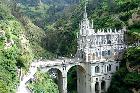"""The Las Lajas Cathedral is located in southern Colombia and built in 1916 inside the canyon of the Guaitara River. According to the legend, this was the place where an indian woman named María Mueses de Quiñones was carrying her deaf-mute daughter Rosa on her back near Las Lajas (""""The Rocks""""). Weary of the climb, the María sat down on a rock when Rosa spoke (for the first time) about an apparition in a cave."""