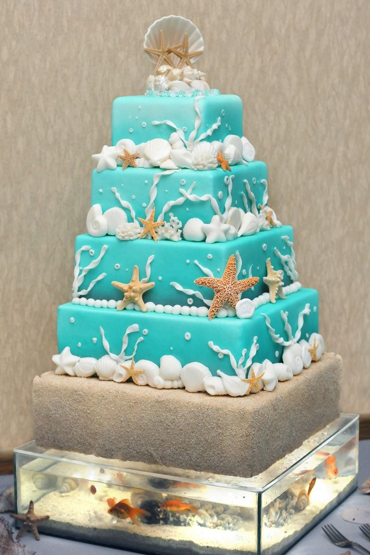 Beach Themed Wedding Cake on top of custom made fish tank base (with real fish!). Lights are integrated in the cake and operated by remote-less switch