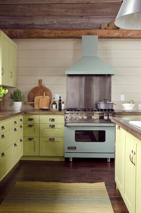 Beautiful kitchen with reclaimed barn board ceilings over whitewashed pine tongue and groove clad walls and dark hardwood floors layered with a green and blue rug.
