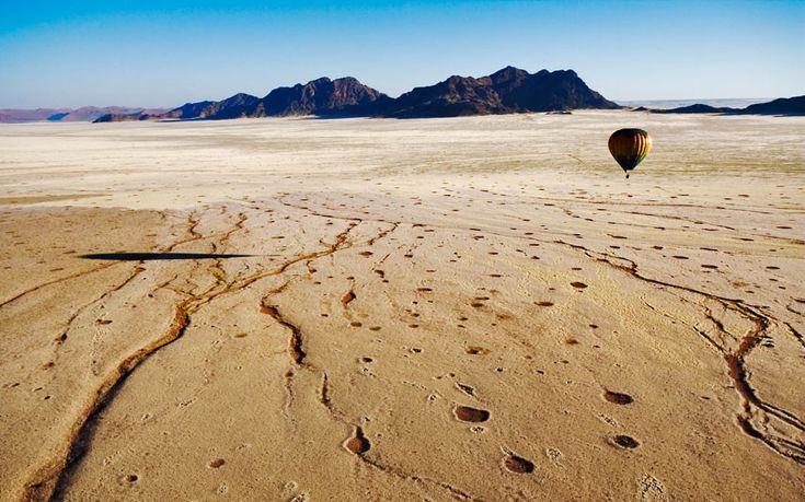A hot-air balloon floats over the Namib desert