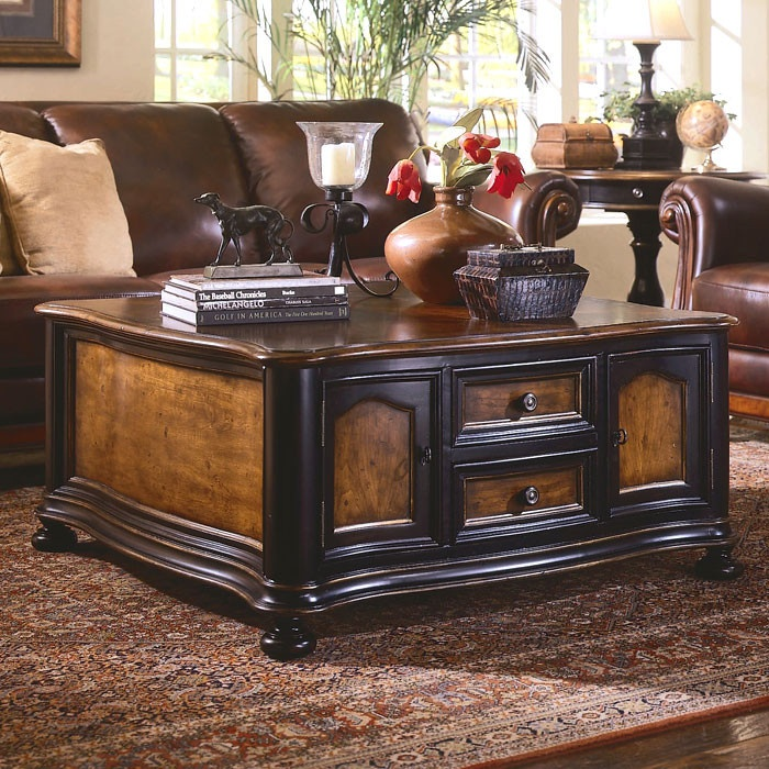 hooker brand distressed hardwood coffee table with 4 doors and 4 drawers finished in contrasting cherry and black rubthrough