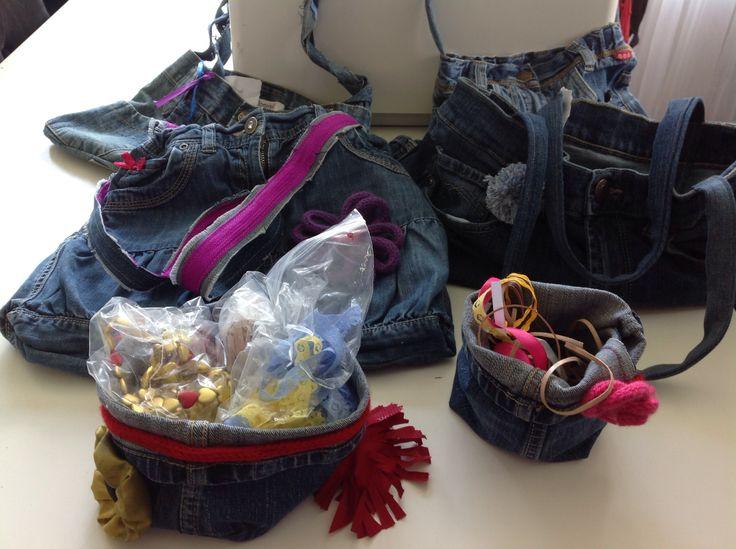 Vier tassen en twee mandjes gemaakt in 3 handvaardigheidslessen van oude spijkerbroeken. De kinderen knipten en spelden het vast. Na het stikken op de naaimachine door mij, zijn de kinderen met de hand de tassen gaan versieren met lintjes, pomponnetjes, kraaltjes en borduren.