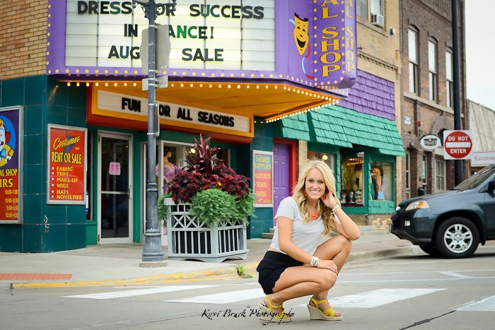 2014 High School Senior girl for posing picture ideas. Senior girl posing in an urban or downtown setting with bright colors, buildings and a theater background.  High school senior session pose inspiration for senior pictures.